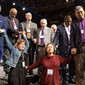 Florida delegates Rachael Sumner (front left) and the Rev. Jacqueline Leveron (front right) of the Florida Conference join in prayer with bishops and other delegates before a key vote on church policies about homosexuality during the 2019 United Methodist General Conference in St. Louis. Photo by Mike DuBose, UMNS.