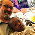 Paul Bowman sits with a child he met at the Uganda-South Sudan Annual Conference in September.