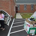 Amanda Queen, right, carries baby supplies to her car while her stepdaughter, Emery, admires a tiny outfit.